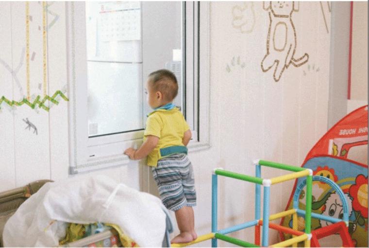 厨房のママを見つめる赤ちゃん