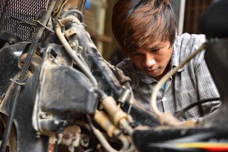 バイク修理の職業訓練に取り組む少年の写真
